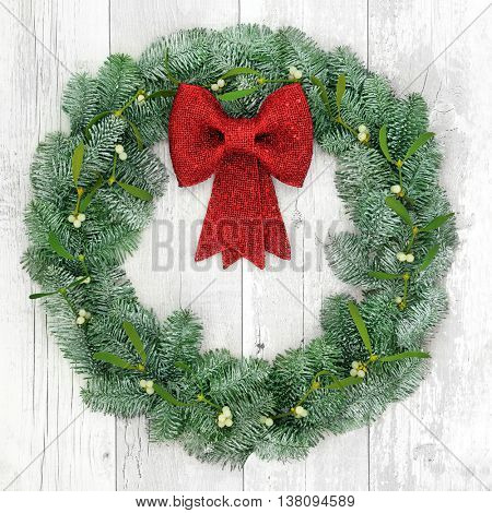 Christmas wreath with red bow decoration, mistletoe and snow covered blue spruce fir over distressed white wood background.