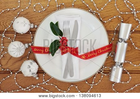 Christmas table setting with white porcelain plate, knife and fork, linen serviette, merry christmas red ribbon, silver bauble decorations and cracker over oak background.