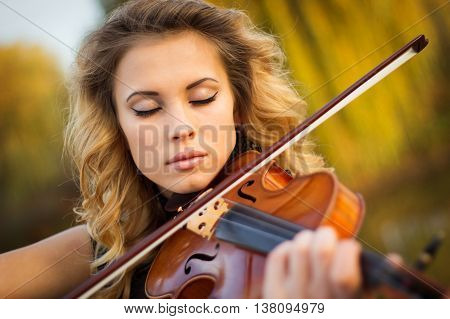 Young woman playing the violin at park. Shallow depth of field.