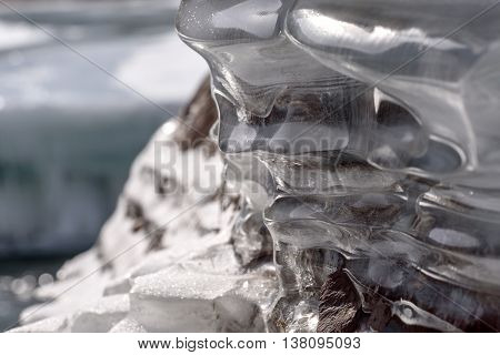 Abstract spring nature background with a pattern of ice on the stones on the shore of a mountain river