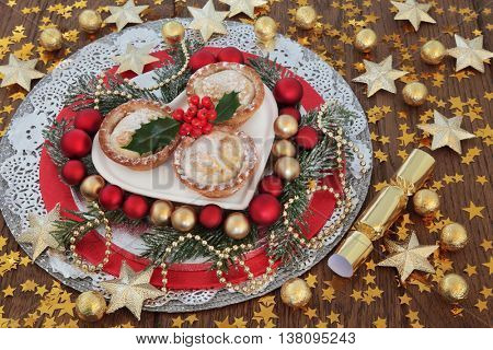 Christmas food still life with mince pie cake, holly, red and gold round and star bauble decorations, winter greenery and stars over oak background.