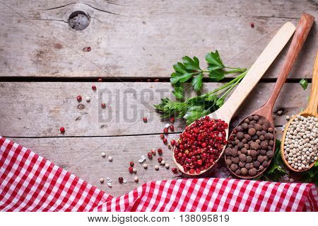 Seasoning for cooking. Red white and allspice pepper in wooden spoons on aged wooden background. Food ingredient. Selective focus. Flat lay. Place for text.