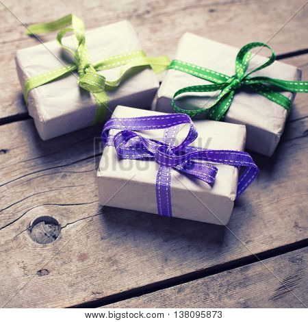 Three festive gift boxes with presents on aged wooden background. Selective focus. Place for text. Toned image.