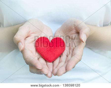 Closeup red heart shape fabric on woman hands