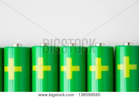 recycling, energy, power, environment and ecology concept - close up of green alkaline batteries