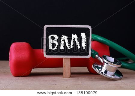 Medical concept - Stethoscope and dumbbell on wood with BMI word