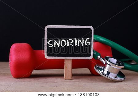 Medical concept - Stethoscope and dumbbell on wood with Snoring word