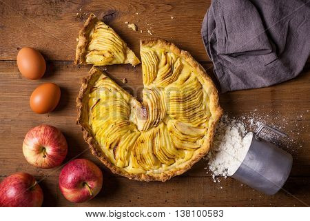 A homemade apple pie made with cream on a wooden kitchen table with apples eggs and flour.