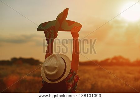 Happy kid playing with toy airplane on sunset background