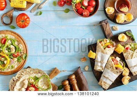 Tortilla with grilled chicken fillet and different vegetables on blue wooden table with copy space. Top view. Outdoors Food Concept