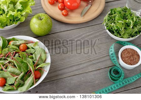 Different salad leaves flax seeds tomato green apple a glass of water and measuring tape on a wooden table with copy space. Dietary products