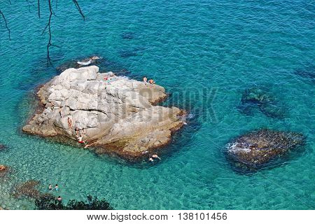 Lloret de Mar - July 9, 2016: People swimming in the transparent waters around a small island next to Cala Boadella, one of the best beaches in Costa Brava