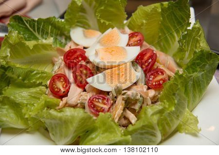 A Salad of lettuce sausage and boiled eggs