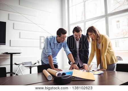 Businessman explaining blueprint to coworkers at creative office