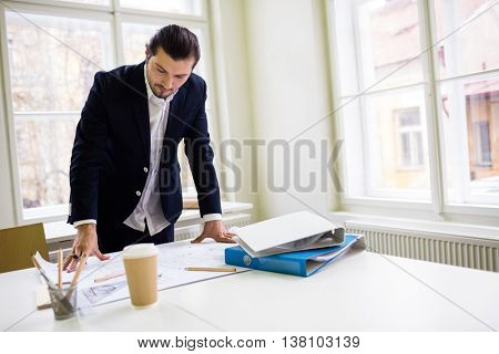 Interior designer looking at blueprint on table in creative office