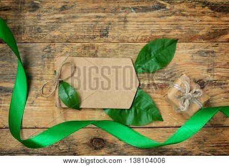 Blank paper tag with foliage gift box green silk ribbon on the old wooden table