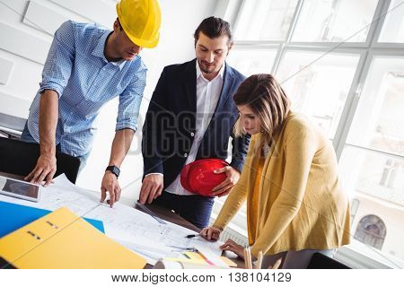 Tilt image of business people looking at blueprint on table at creative office
