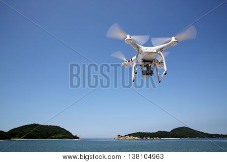 KAGAWA, JAPAN - July 6, 2016: White remote controlled Drone Dji Phantom 3 equipped with high resolution video camera hovering in air with sea and clear blue sky in the background