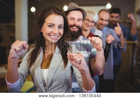 Coworkers cheering with clenched fist while standing in row at creative office