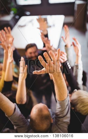 High angle view of business people cheering in creative office