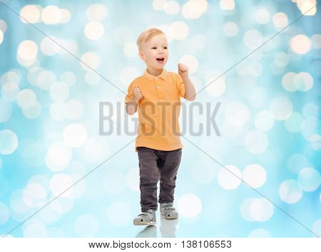 childhood, fashion, emotion, expression and people concept - happy little boy in casual clothes having fun over blue holidays lights background