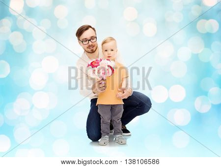 family, childhood, fatherhood, holidays and people concept - happy father and and little son with bunch of flowers over blue holidays lights background