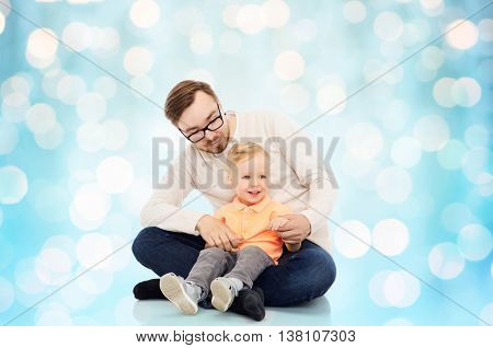 family, childhood, fatherhood, leisure and people concept - happy father and and little son over blue holidays lights background