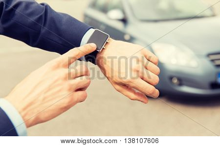 transport, business trip, technology, time and people concept - close up of male hands with wristwatch on car parking