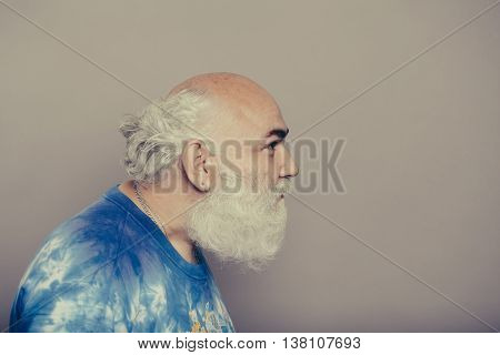Old man with grey beard and bald hairless head with silver earrings in blue t-shirt indoors