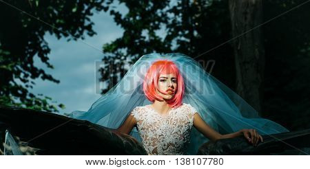 young pretty woman with orange or pink hair and bright makeup in white wedding suit and blue bride veil on natural background outdoor near stony statue wings