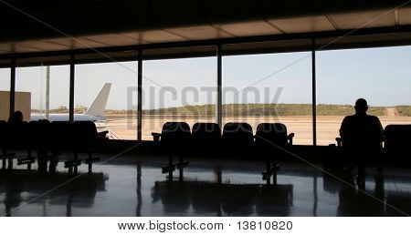 Male silhouette in the waiting lounge in airport