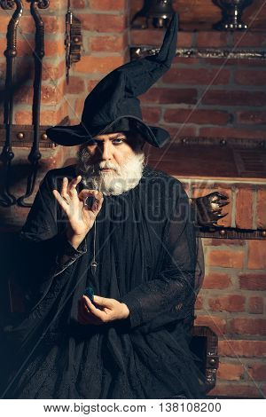 Old wizard with pendulum in black costume and hat for Halloween on kitchen background
