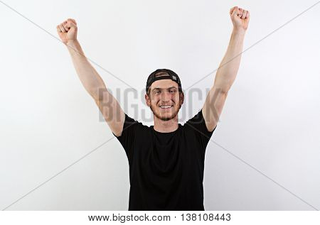 Smiling Young Adult Male in Dark T-Shirt and Baseball Hat Worn Backwards with Arms Raised