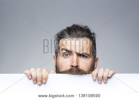 young man with serious face with long hair behind white paper sheet in studio on grey background copy space