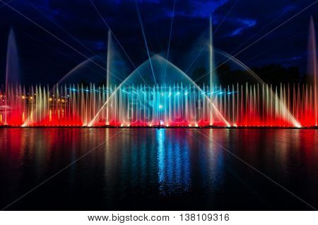 Night magic show of fountains on the central waterfront Roshen Ukrainian city of Vinnitsa