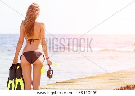Young slim woman with snorkelling equipment standing near sea. Caucasian girl with flippers mask and snorkel. Scuba diving or snorkel background