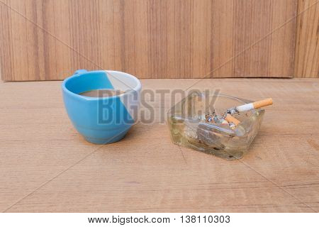 coffee with cigarette an ashtray on the wood table