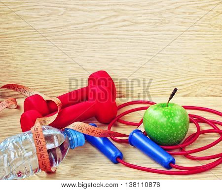 dumbbells apple bottle of water measuring tape and jump rope on wooden panels fitness concept