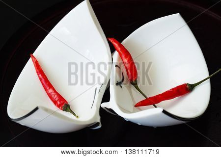 Broken white cup on black background with red chili peppers. Concept for divorce, relationships, friendships