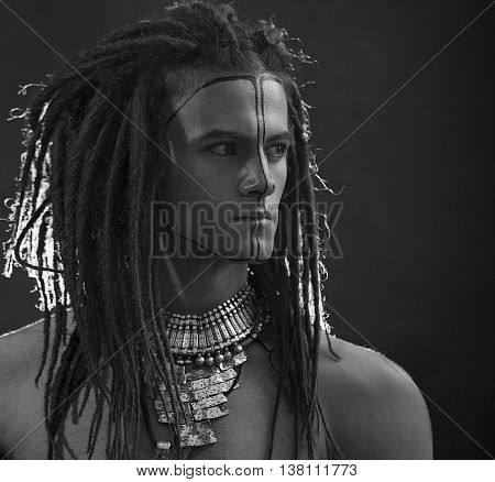 Young man's portrait. Stylish handsome sexy Guy with Dreadlocks and ethnic Jewelry Accessories (necklace bracelet) Close-up face. Tribal Style. Trendy youthful man's look, war paint