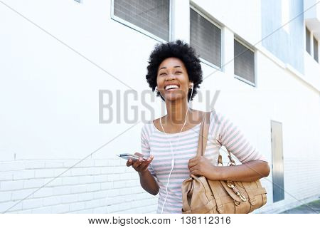 Woman Walking On Sidewalk With Mp3 Player And Purse