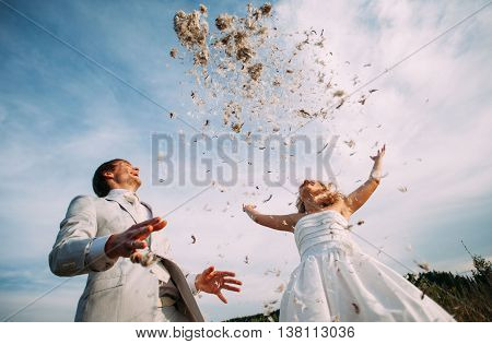 bride and groom are fighting pillows outdoor. Fun newlyweds during a photo shoot. Vintage style