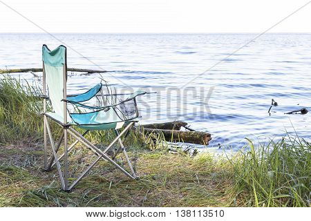 Camping place with armchairs and wooden benches near the sea in summer forest. Camping. Holidays on nature outdoors.