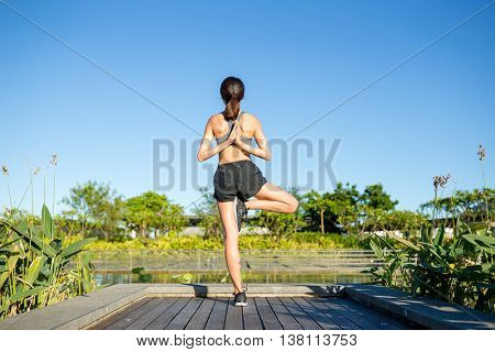 Woman doing yoga pose with hands behind her back