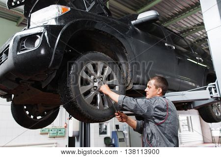 Mechanic diagnosing car wheel with screwdriver. Car maintenance in garage. Young auto service worker fixing wheel on raised on hoist car.