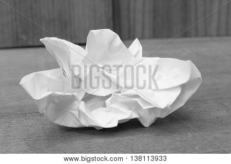 Monochrome paper ball white sheet crumpled lumpy on wooden floor background