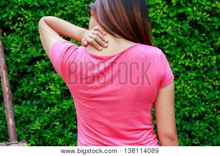 Woman neck pain or shoulder pain in garden concept