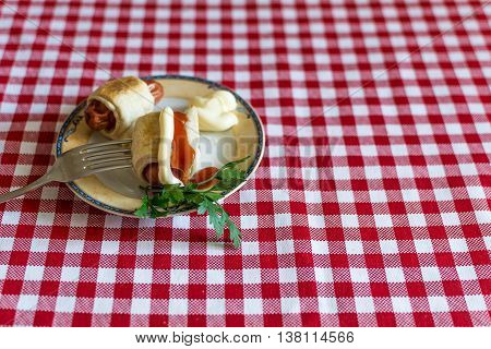 Sausages in dough ( Mini hot dog homemade ) with ketchup, mayonnaise and parsley on a plate. Sausage dough grilled furnace or in a furnace.