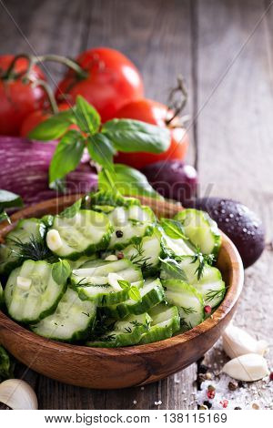 Pickled cucumber with dill and garlick in a rustic wooden bowl