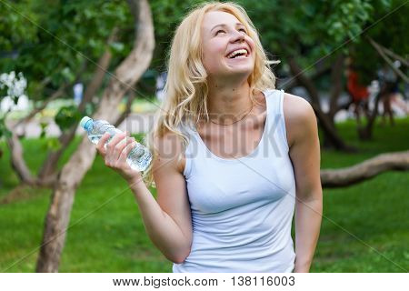 Cute girl in white clothes and with water bottle having fun in park